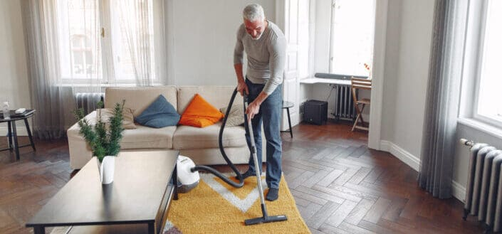 Senior guy vacuuming his rug - how to become a minimalist