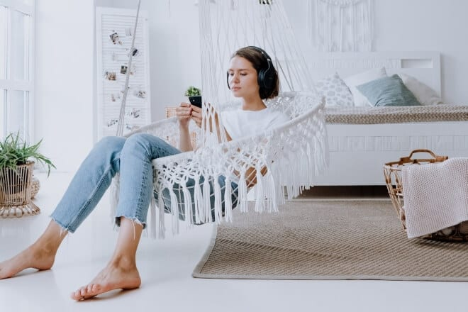 Girl sitting on white hammock swing while listening to music on her phone - how to become a minimalist
