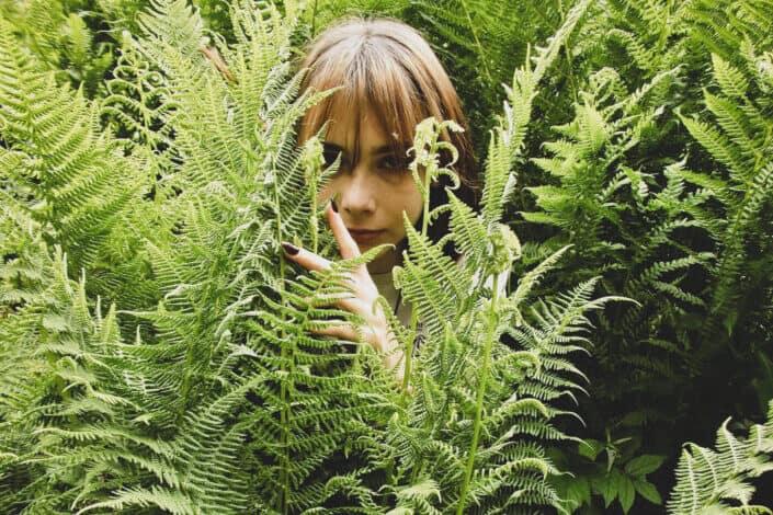 girl partially hidden by ferns