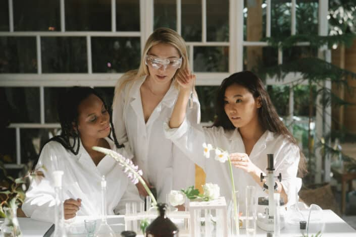 women wearing lab coat collaborating