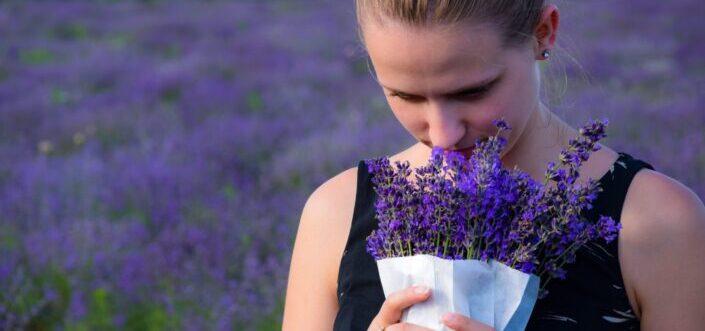 A woman smelling bouquet of purple lavender