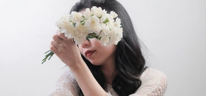 A petite woman holding flowers in front of her face